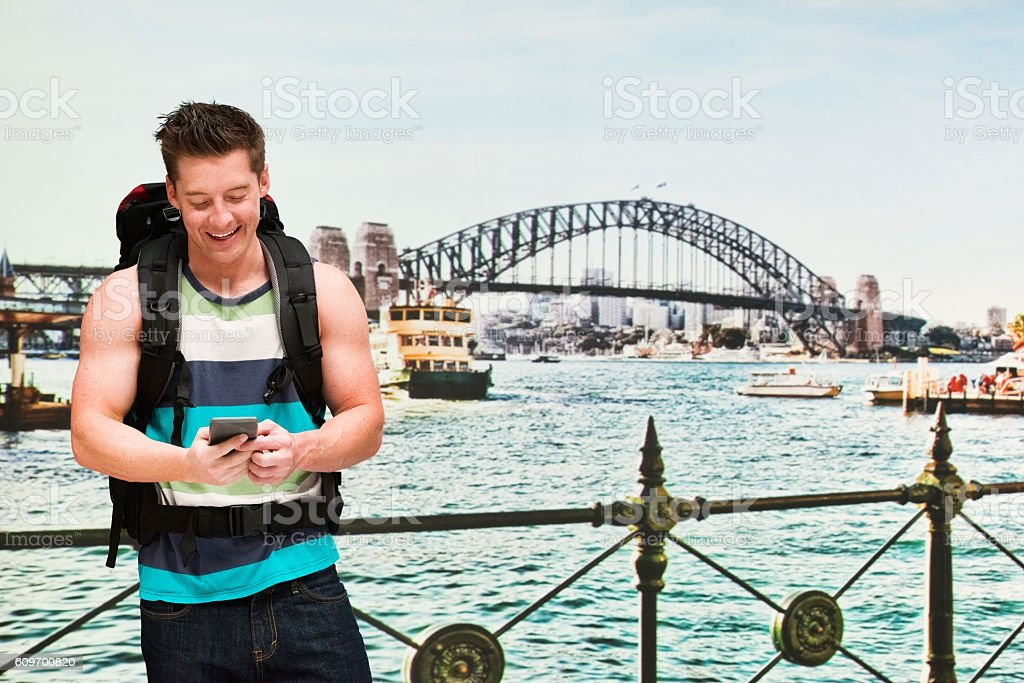 Smiling backpacker using phone outdoors stock photo