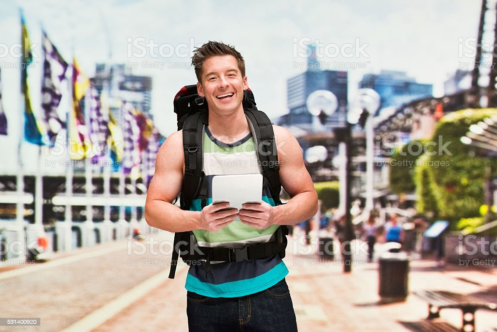 Smiling backpacker using tablet outdoors stock photo