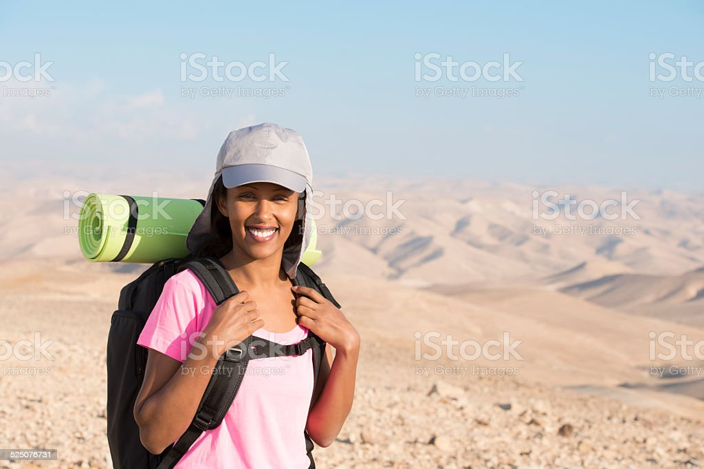 Smiling Backpacker woman in the desert. stock photo