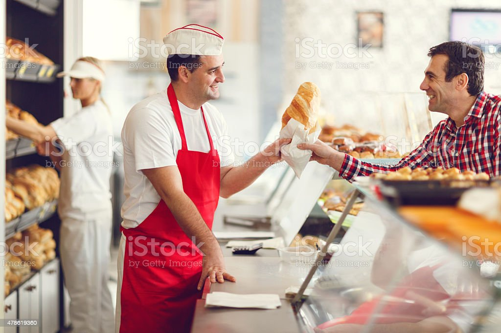 Smiling baker and his customer in bakery. stock photo