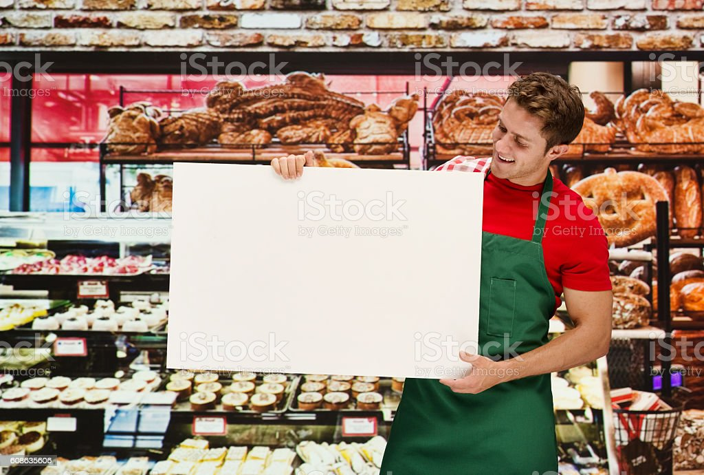 Smiling baker holding placard in bakery stock photo