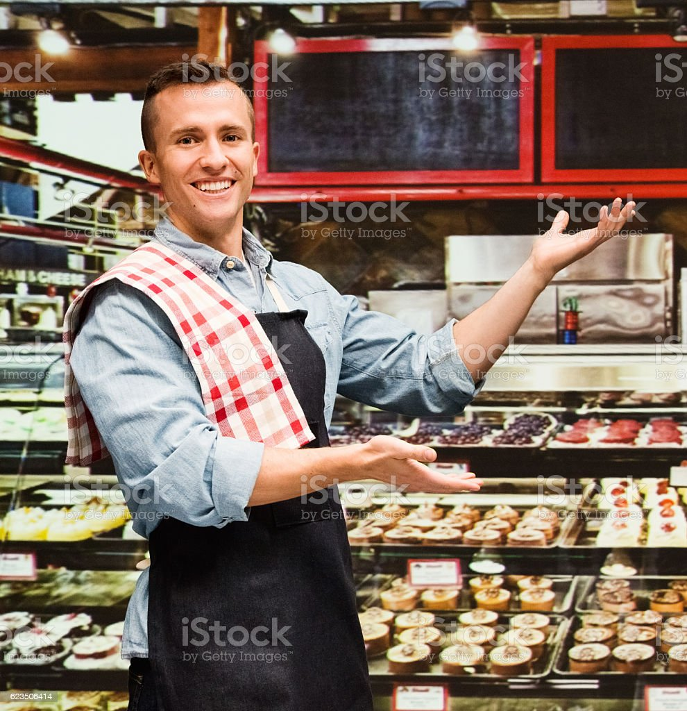 Smiling baker presenting in bakery stock photo