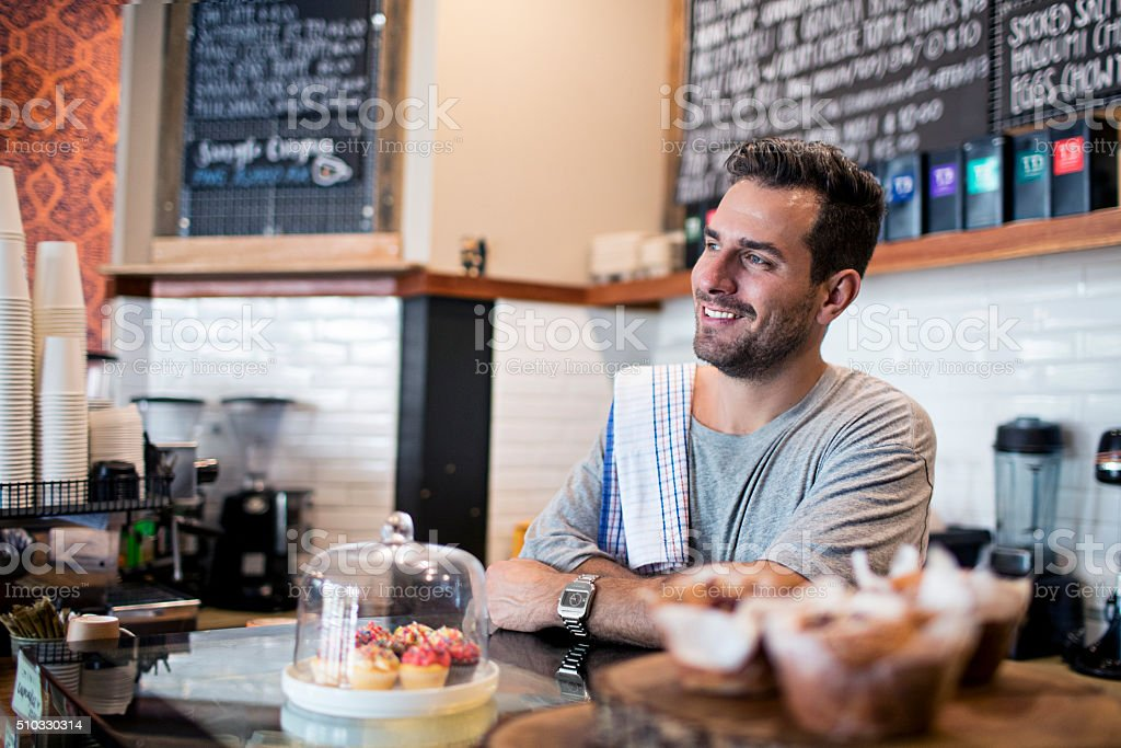 Smiling barista at coffee shop counter stock photo