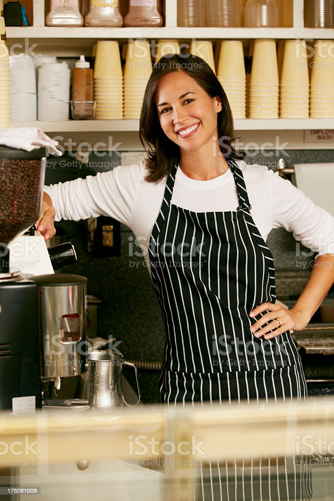 Smiling barista in striped apron leaning on counter royalty-free stock photo