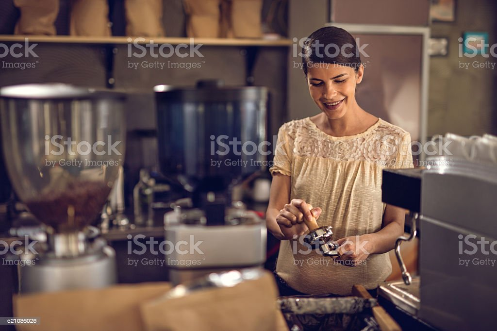 Smiling barista making coffee in a cafe. stock photo