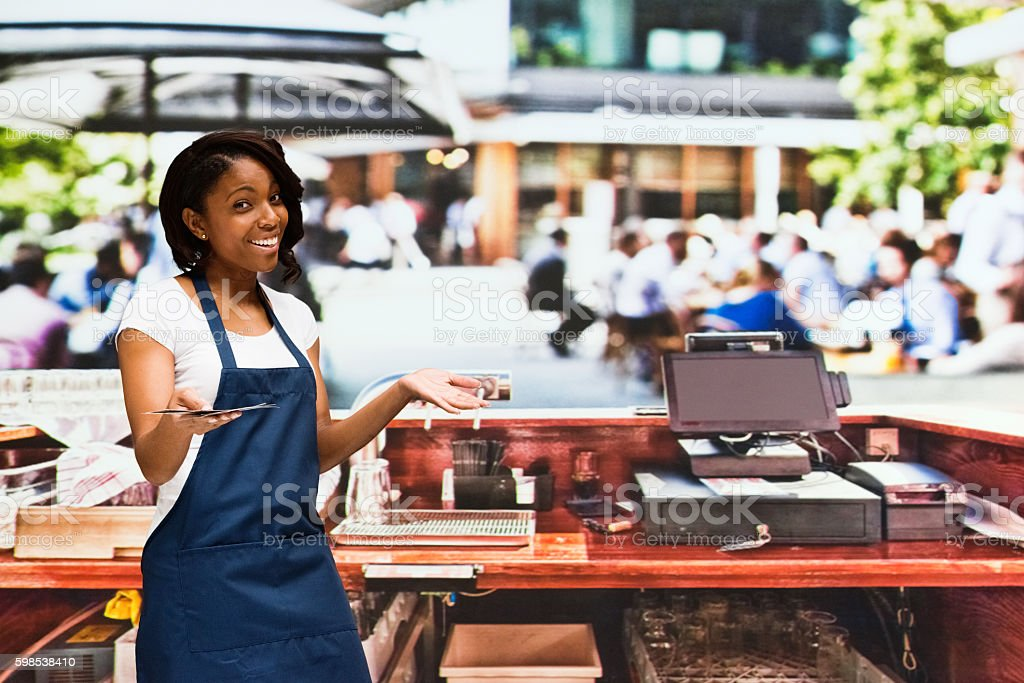 Smiling bartender holding cash outdoors stock photo