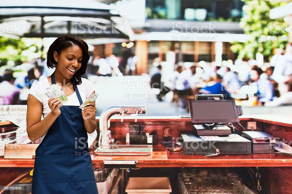Smiling bartender holding European money stock photo