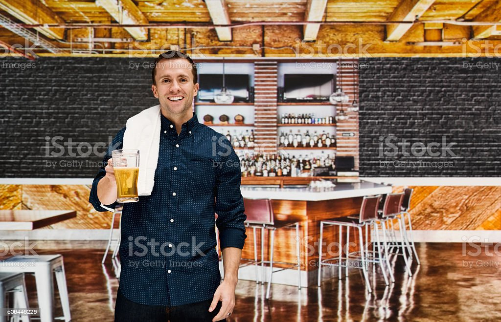 Smiling bartender holding glass in bar stock photo