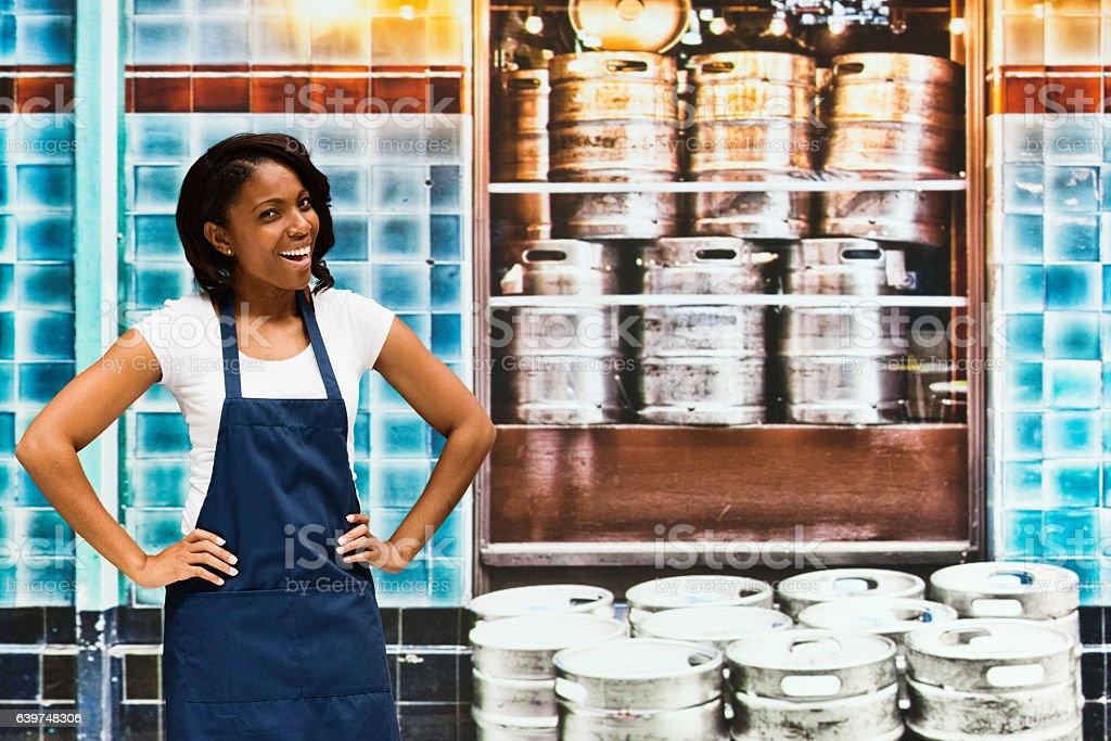 Smiling bartender standing in bar stock photo