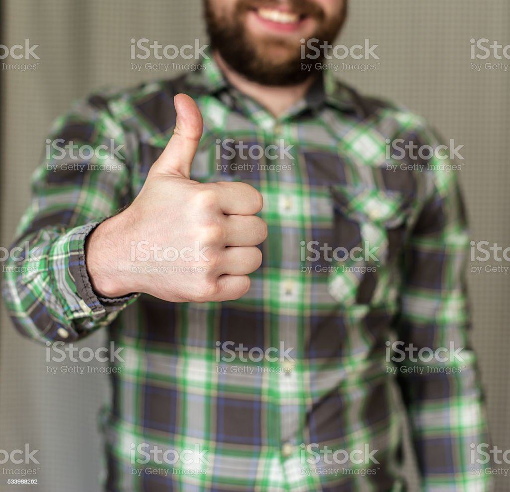 smiling, bearded man in a checkered shirt did a thumbs-up stock photo