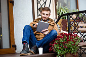 Smiling bearded man sitting on porch near entrance using tablet