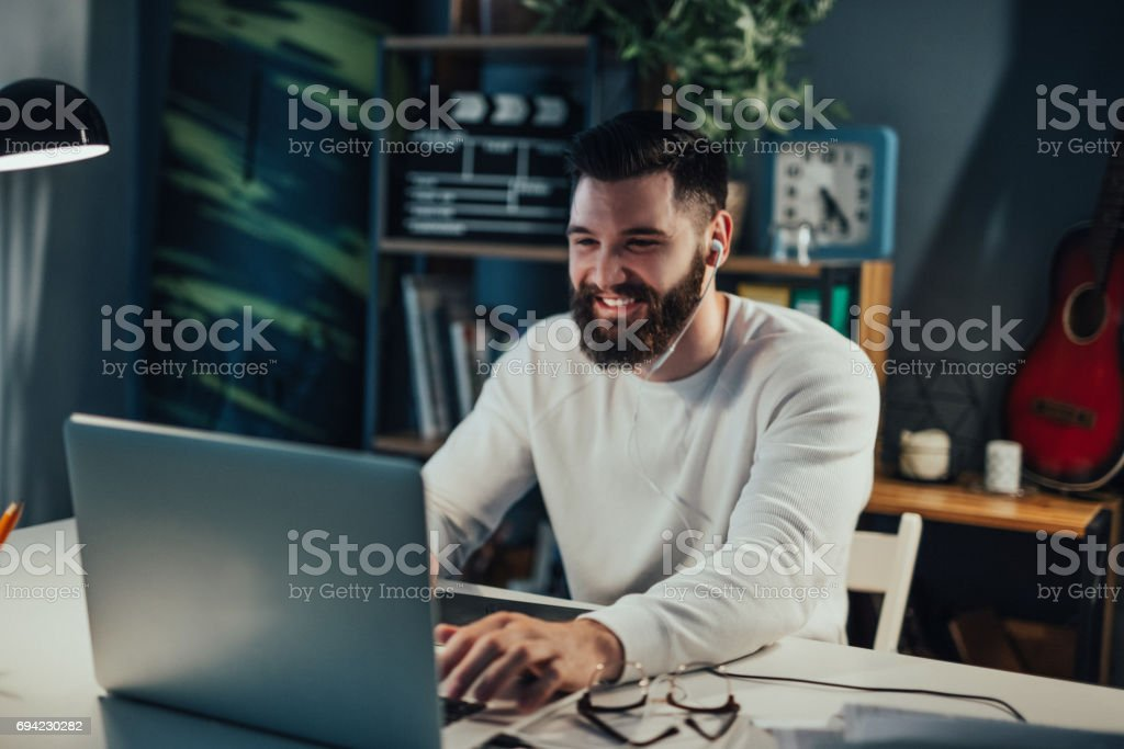 Smiling bearded man using laptop for video call stock photo