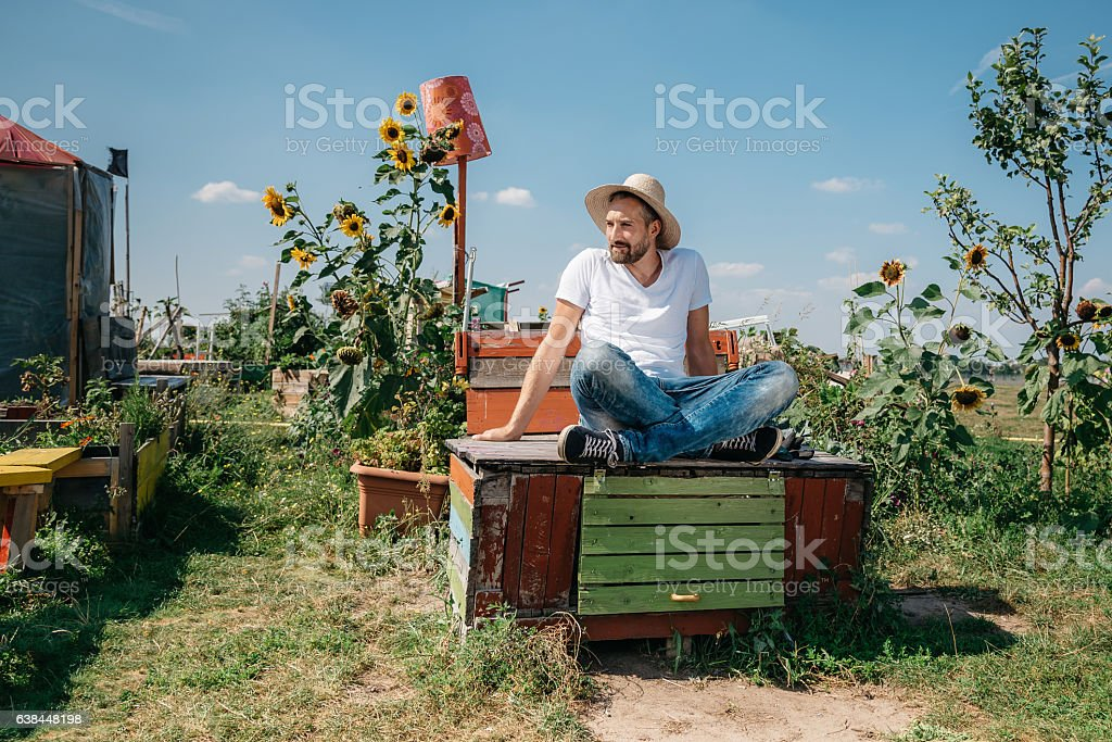 smiling bearded man with sombrero sitting in garden on box stock photo