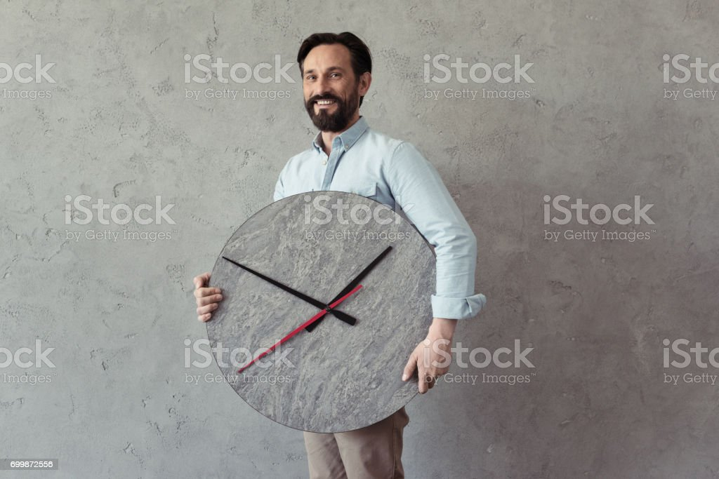 smiling bearded mature man holding clock and looking at camera stock photo