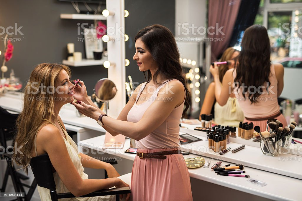 Smiling beautician applying blush on young woman in beauty salon. stock photo