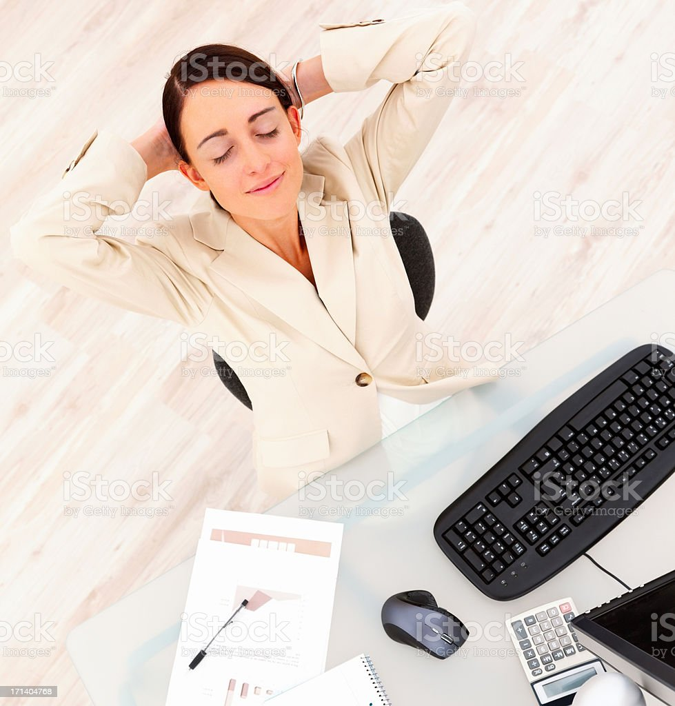 Smiling beautiful business woman relaxing at desk by computer royalty-free stock photo