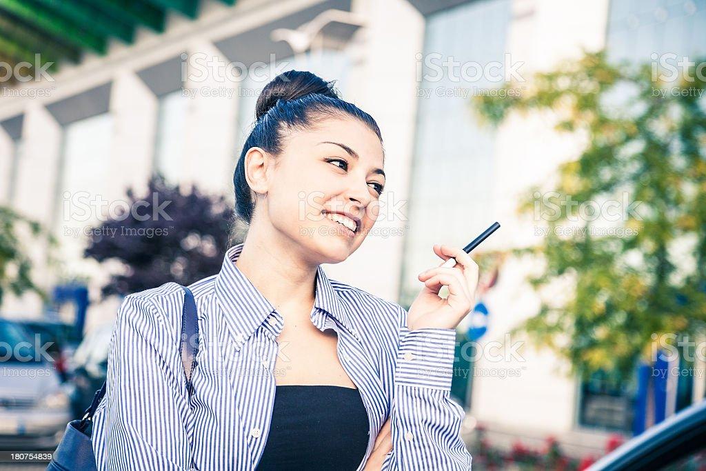 Smiling beautiful girl smoking E-cigarette royalty-free stock photo