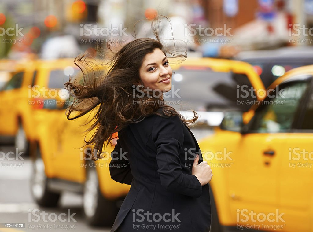Smiling beautiful girl with dispelled hair walking on NY street stock photo