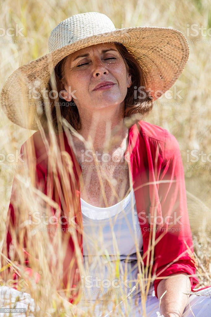 smiling beautiful older woman enjoying sun under straw hat stock photo