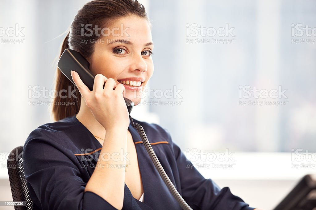Smiling beautiful woman at her workplace talking on the phone. royalty-free stock photo