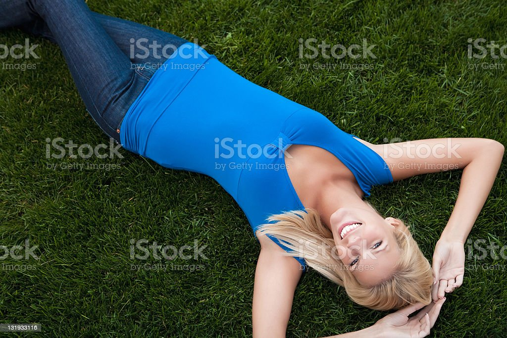 Smiling beautiful woman lying on grass royalty-free stock photo