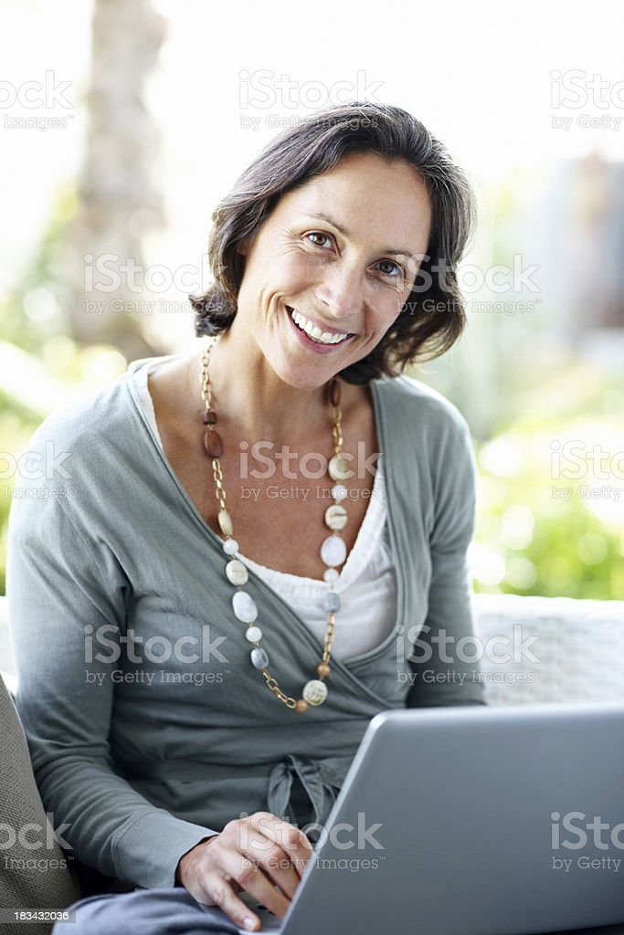 Smiling beautiful woman sitting at home with laptop royalty-free stock photo