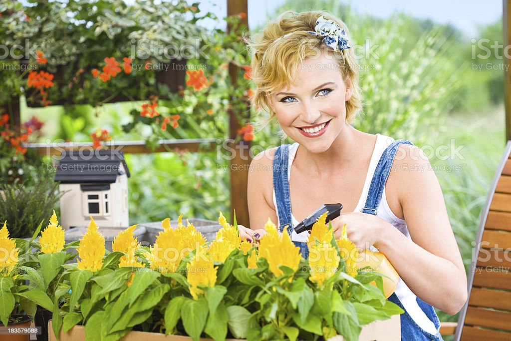 Smiling beautiful woman watering flowers royalty-free stock photo