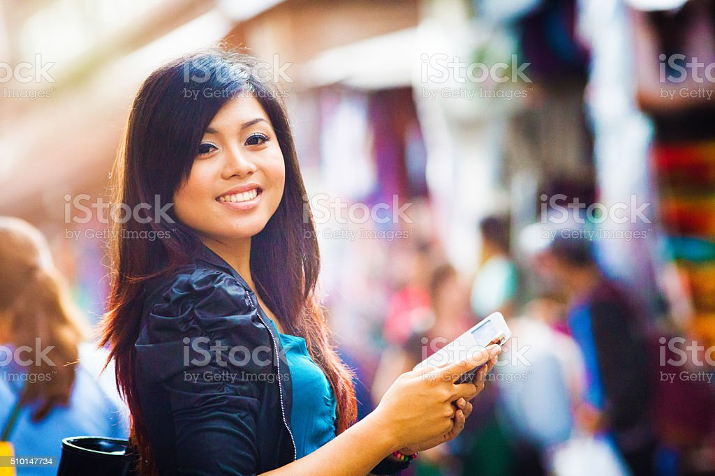 Smiling beautiful young Indonesian woman portrait with phone stock photo