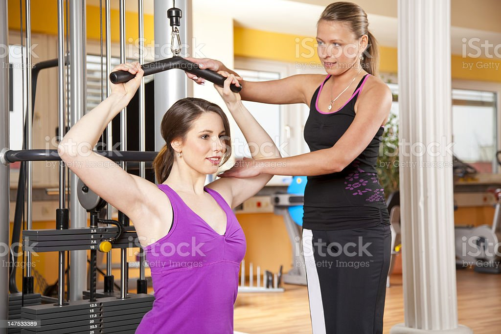smiling beautiful young woman exercising in gym with trainer stock photo