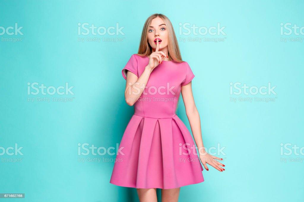 Smiling beautiful young woman in pink mini dress posing at studio stock photo