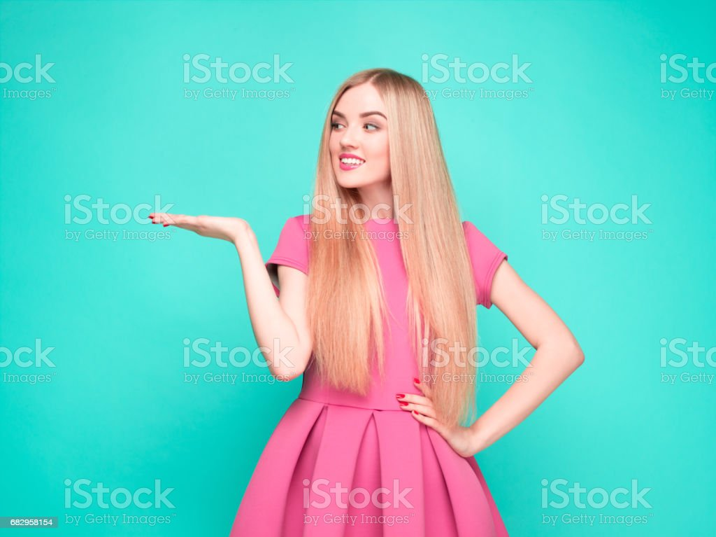 Smiling beautiful young woman in pink mini dress posing, presenting something stock photo