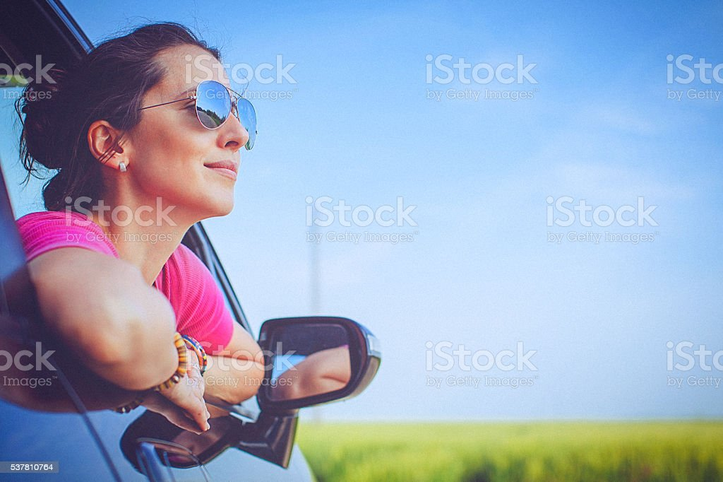 Smiling, beautiful, young woman rests looking out the car window stock photo
