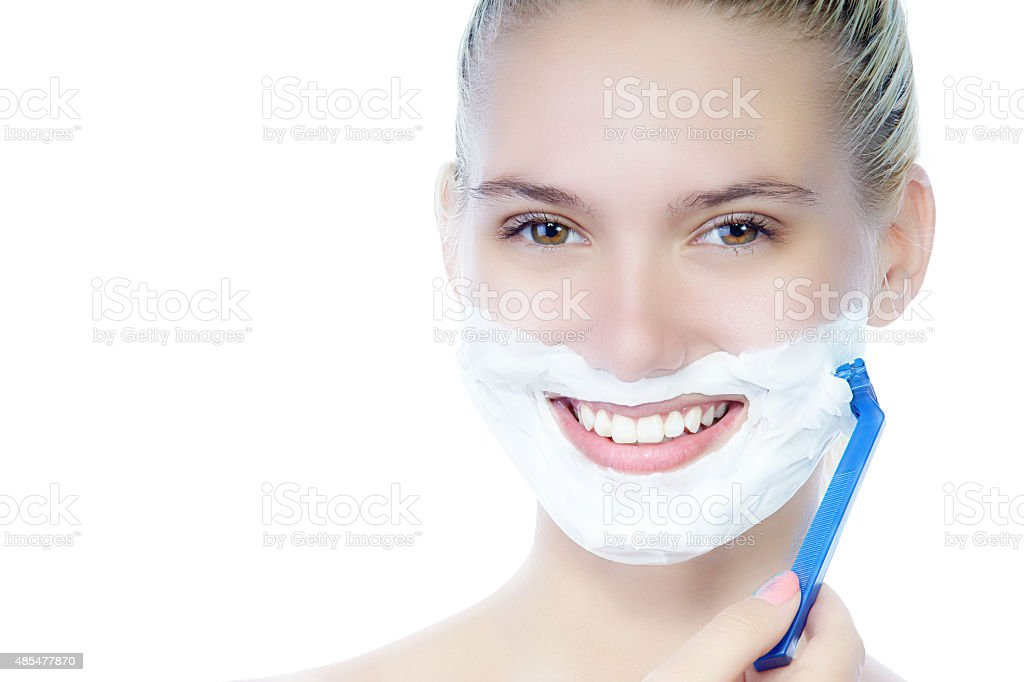 Smiling beautiful young woman shaving face stock photo
