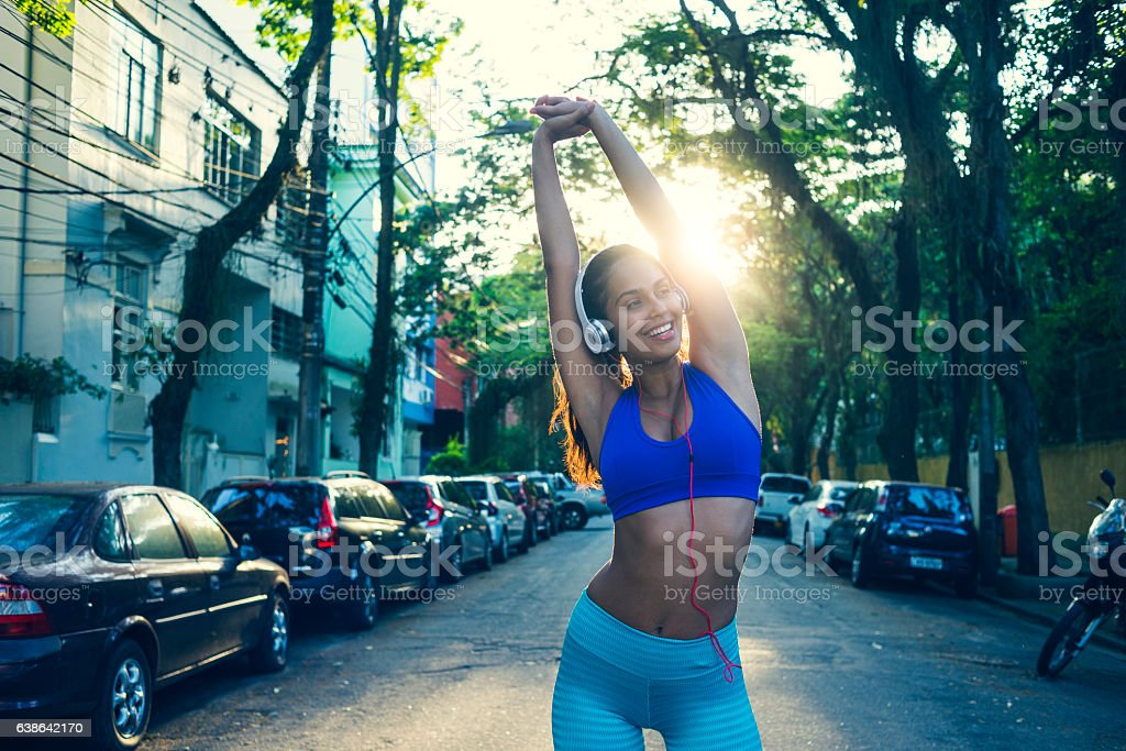 smiling beautiful young woman stretching after workout stock photo