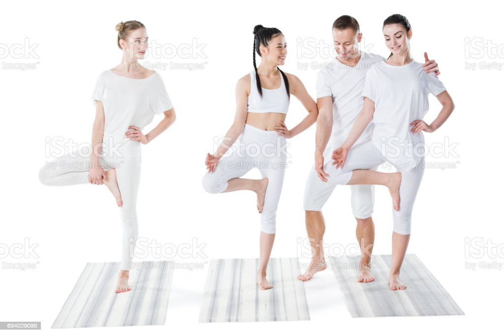 Smiling beautiful young women practicing yoga with trainer isolated on white stock photo
