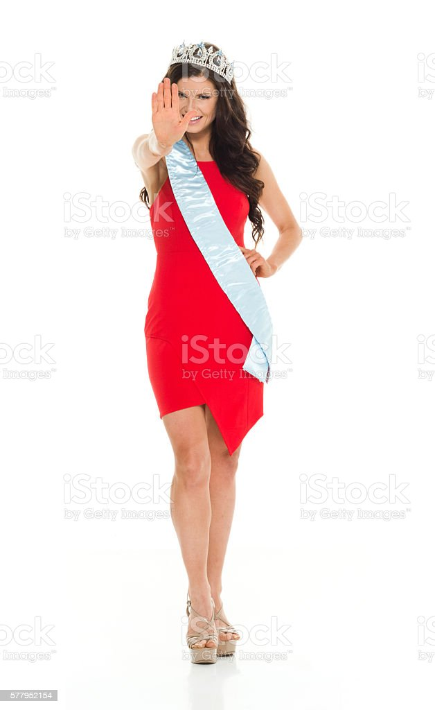 Smiling beauty queen giving stop sign stock photo