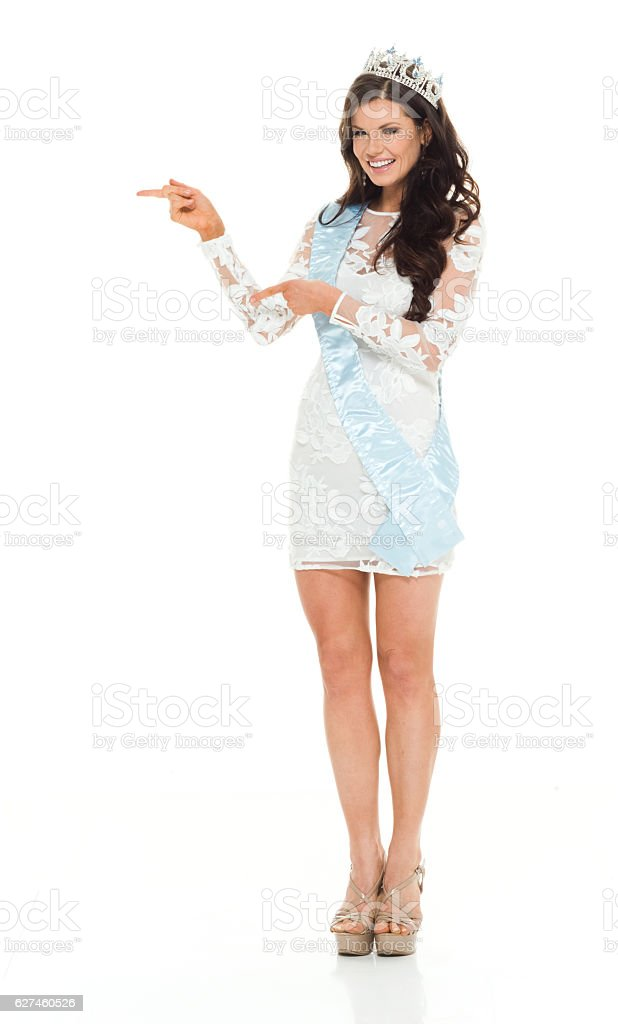 Smiling beauty queen pointing away stock photo