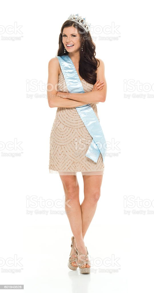 Smiling beauty queen standing with arms crossed stock photo