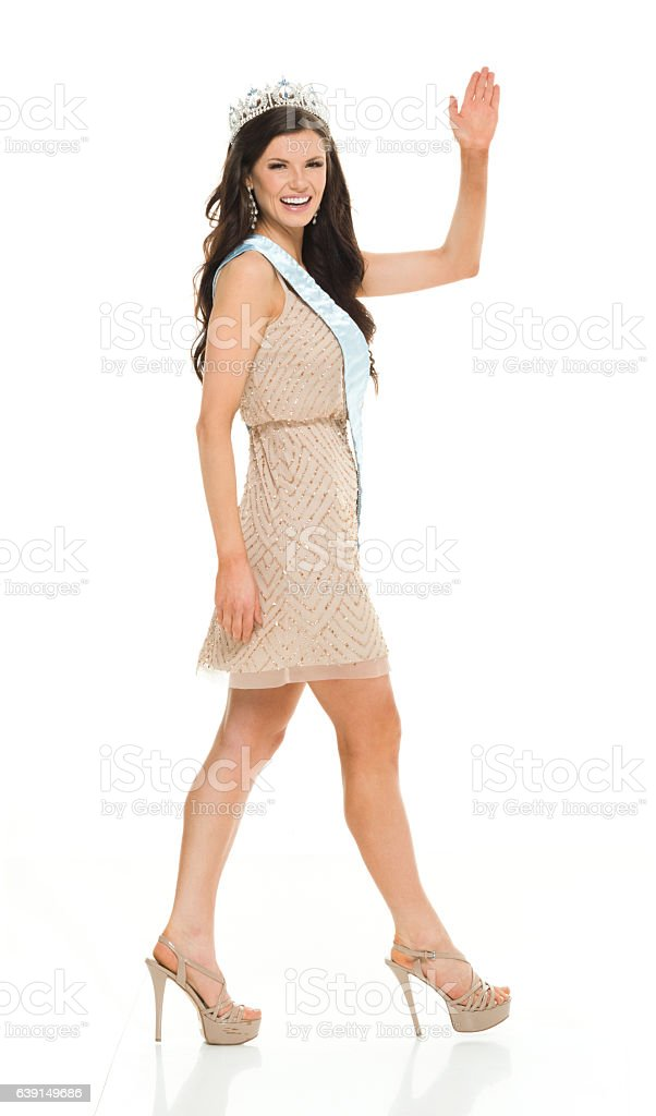 Smiling beauty queen waving hand and walking stock photo