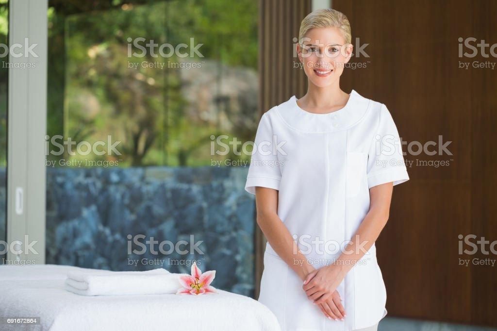 Smiling beauty therapist standing beside massage towel stock photo