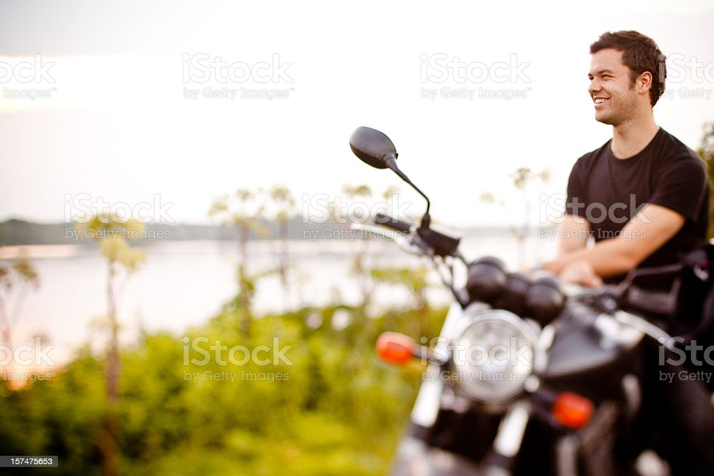 Smiling biker relaxing near a river royalty-free stock photo