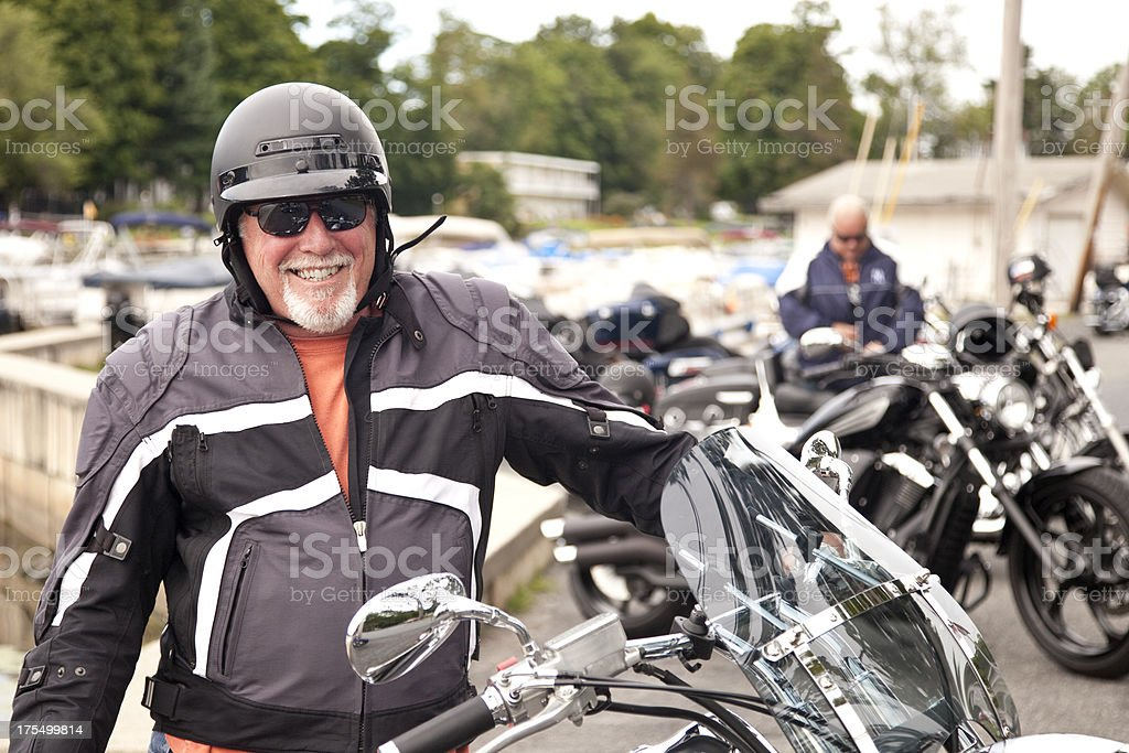 Smiling Biker standing next to motorcycle on a cool day stock photo
