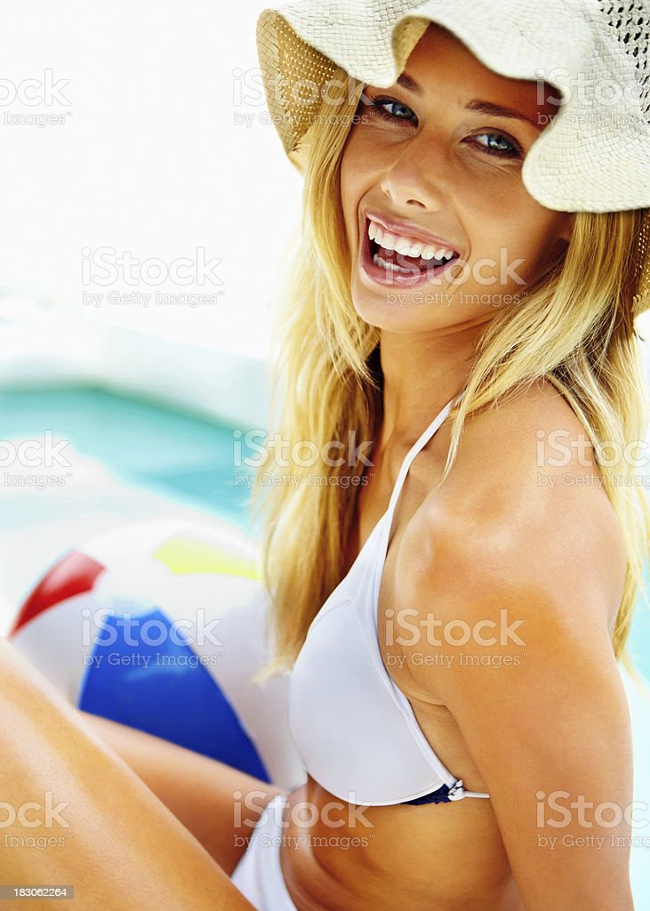 Smiling bikini woman in sun hat by pool with beach-ball stock photo