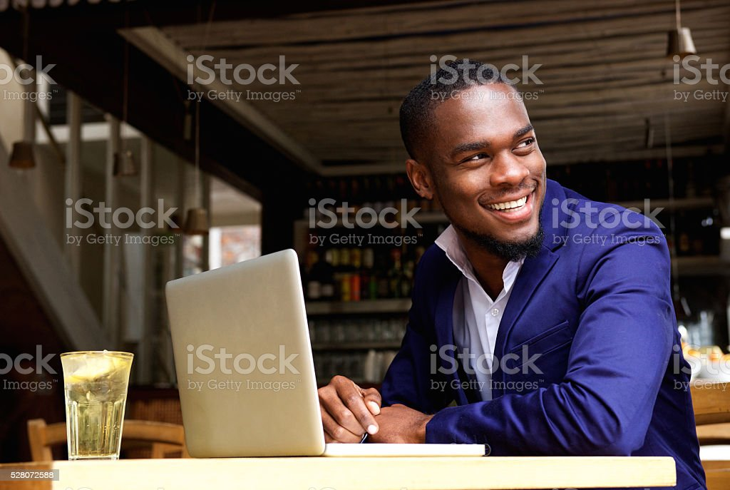 Smiling black businessman with laptop at cafe stock photo