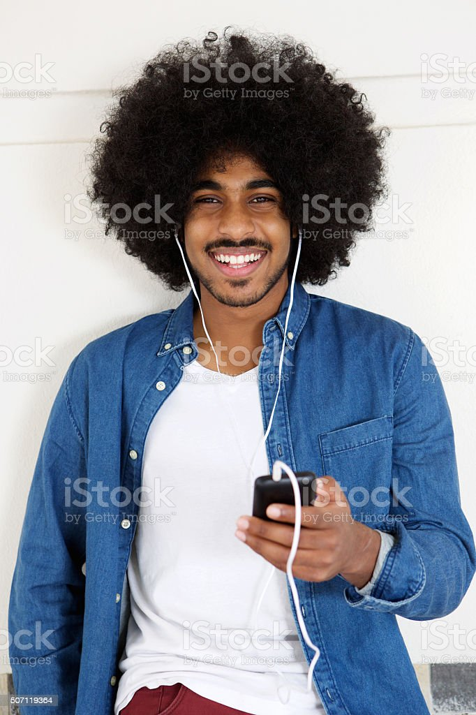 Smiling black guy listening to music on smart phone stock photo