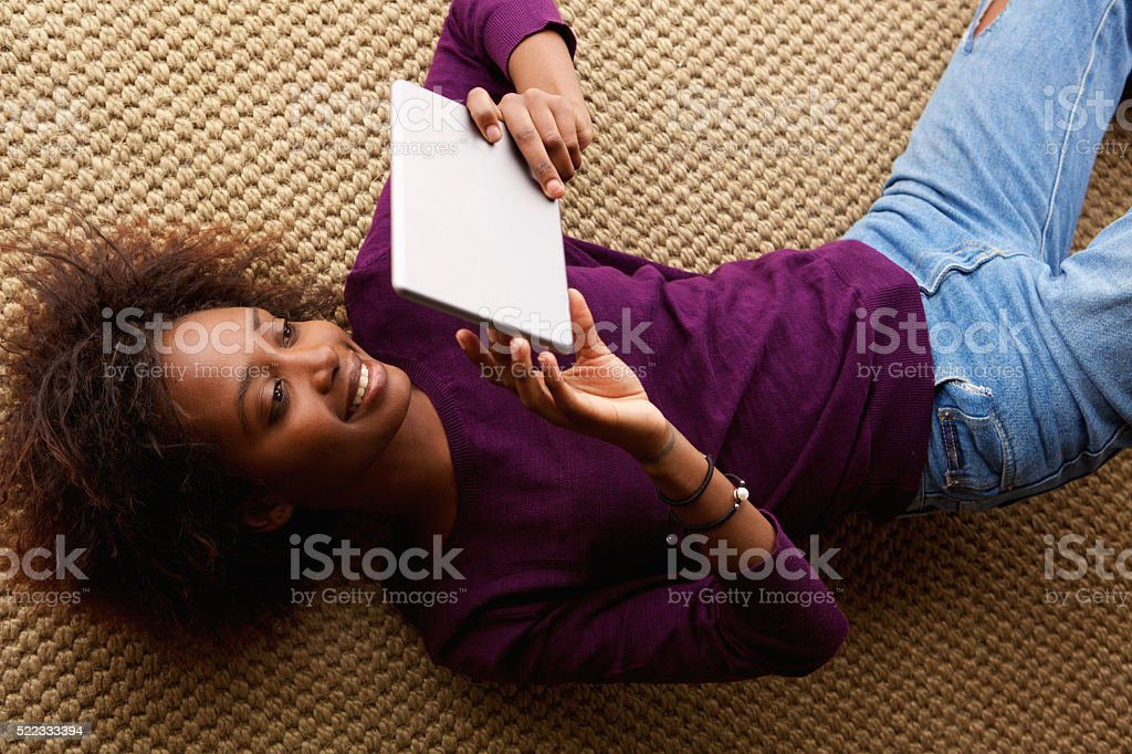 Smiling black woman lying down with digital tablet stock photo