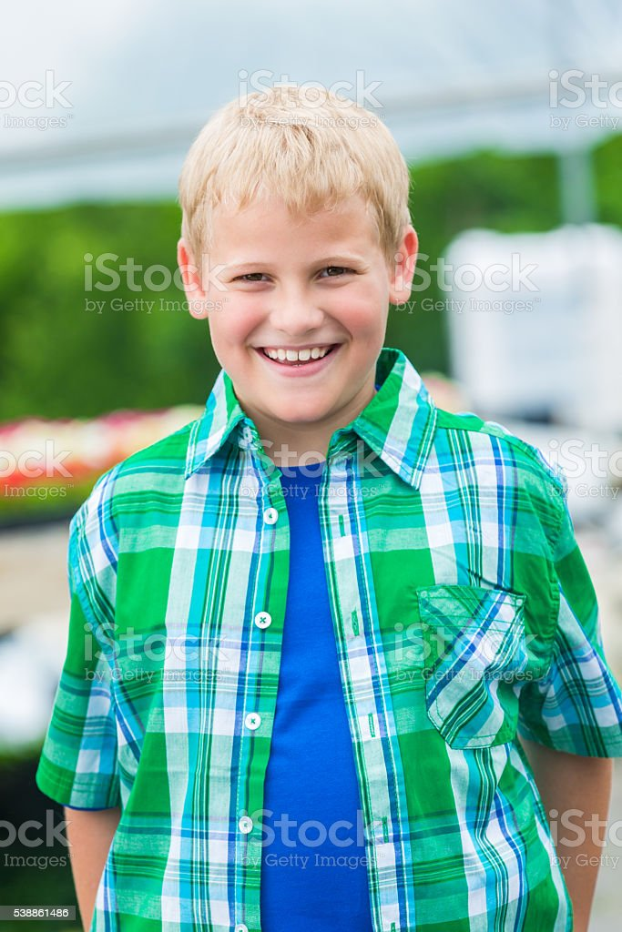 Smiling blond boy in green stock photo