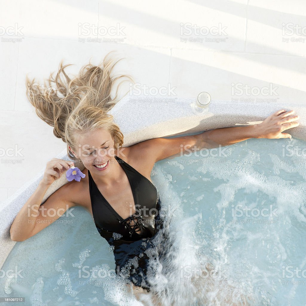 smiling blond hair woman soaking in a resort's jacuzzi royalty-free stock photo