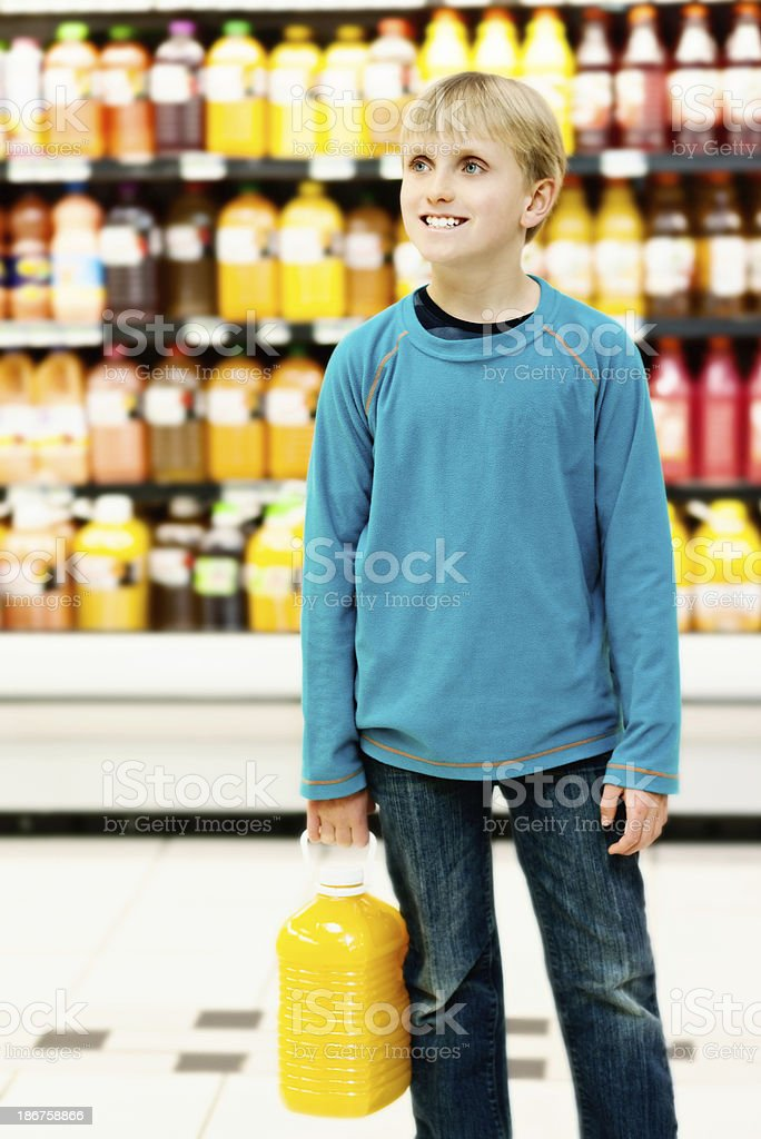 Smiling blond schoolboy fetching orange juice in supermarket royalty-free stock photo