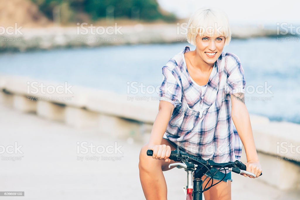 Smiling blond woman cycling next to the sea stock photo